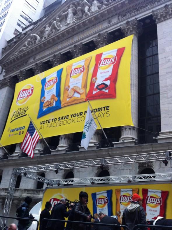"""Voici la mienne... c'est ça New York """"Privatisation de la bourse pour lancement pub"""" Ce n'est pas à Paris que l'on verrait une bâche sur la bourse pour le lancement d'un produit !! Ici : lancement des dernières chips Lays en présence d'Eva Longoria ainsi qu'un poulet bien jaune et d'une chips """"sur pates"""" (costume) ... j'ai des photos !!!! Elsa - 14/02/13 - Wall Street"""